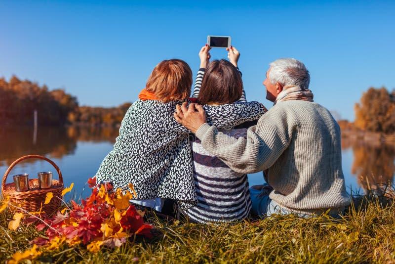 采取selfie的资深父母在有他们的成人女儿的秋天湖之前 家庭价值观 有人野餐 免版税库存图片