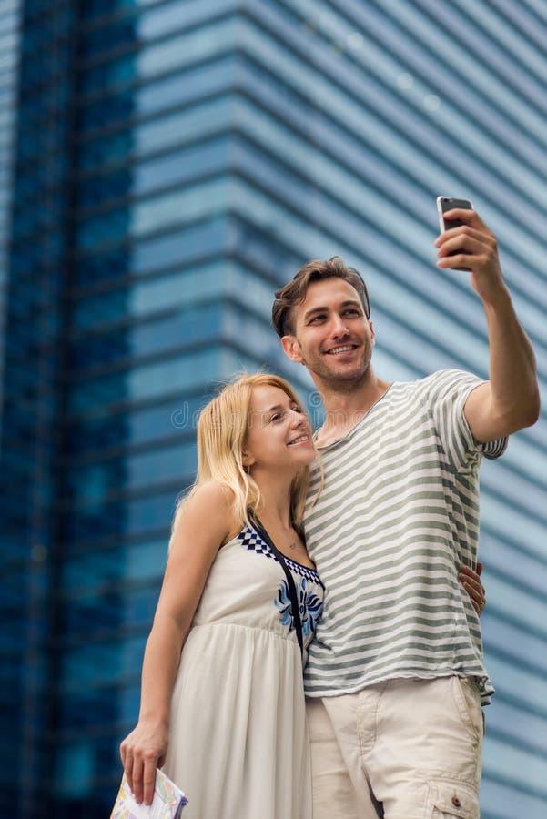 采取selfie的年轻夫妇,当游览外国城市在摩天大楼附近时 免版税库存照片