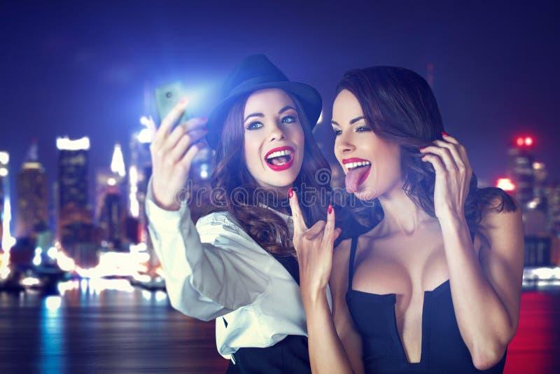 采取selfie的年轻疯狂的女朋友在晚上在城市 免版税图库摄影