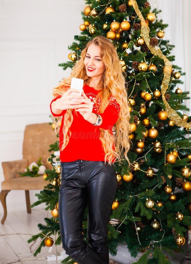 采取selfie的年轻blondy俏丽的妇女在圣诞树附近 免版税库存图片