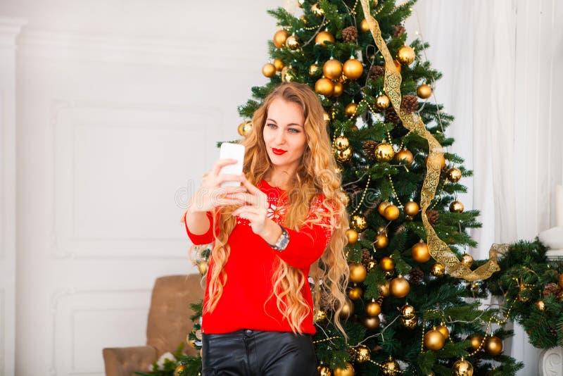 采取selfie的年轻blondy俏丽的妇女在圣诞树附近 免版税图库摄影