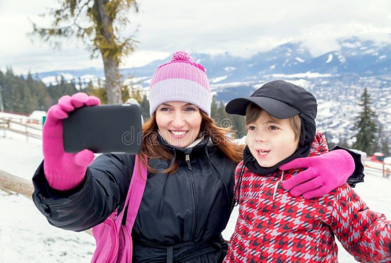 采取selfie!家庭 愉快的做在冬天山的母亲和小男孩自画象 库存照片