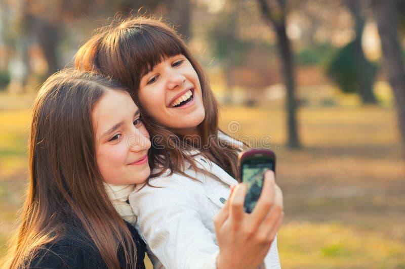 采取selfies的两个十几岁的女孩在公园在晴朗的秋天天 免版税库存照片