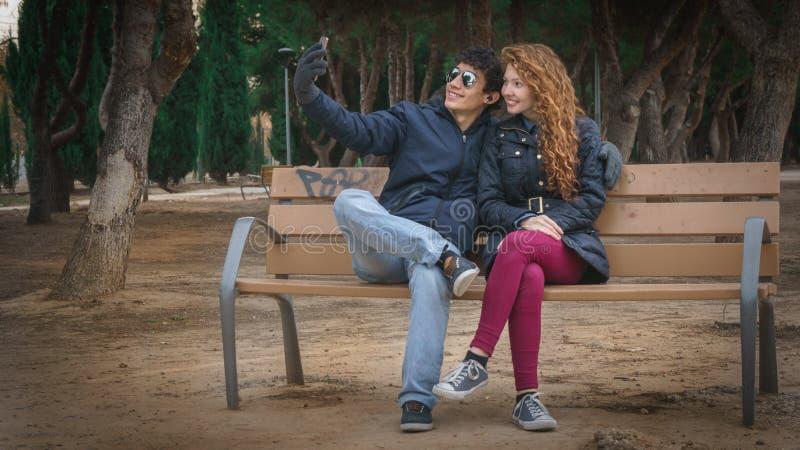 采取selfies的年轻夫妇在winter&的x27公园; s天 免版税库存照片