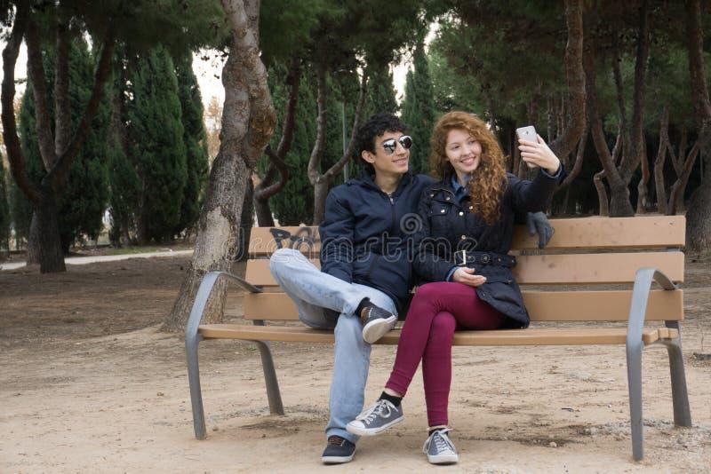 采取selfies的年轻夫妇在winter&的x27公园; s天 图库摄影
