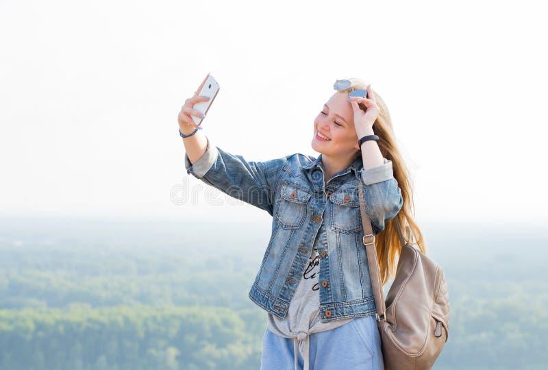 采取selfies的美丽的愉快的白肤金发的女孩户外在公园 免版税库存照片