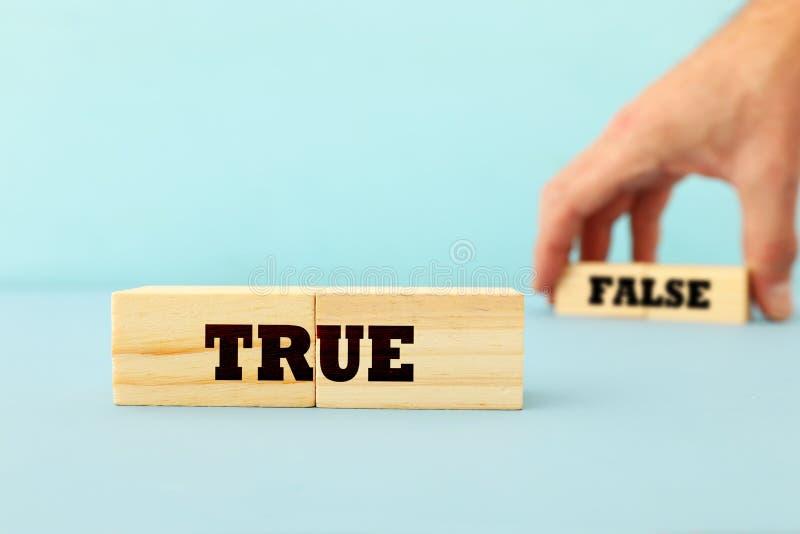 采摘与文本的真实或错误概念人手木立方体在木蓝色背景 库存图片