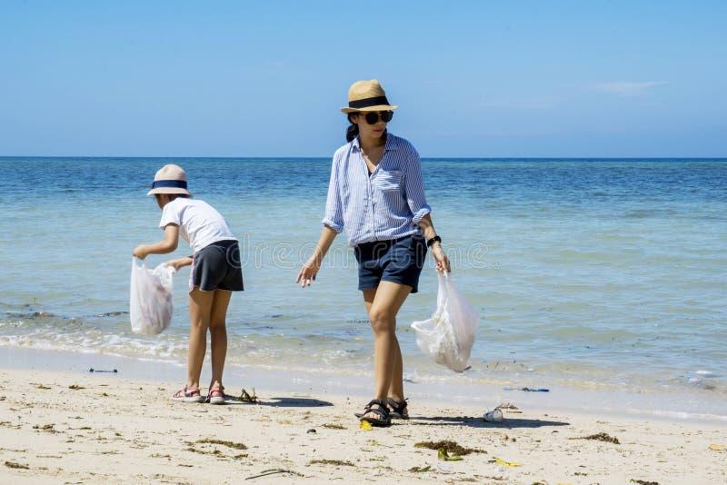 采摘在海滩的两个志愿者塑料废物 库存照片