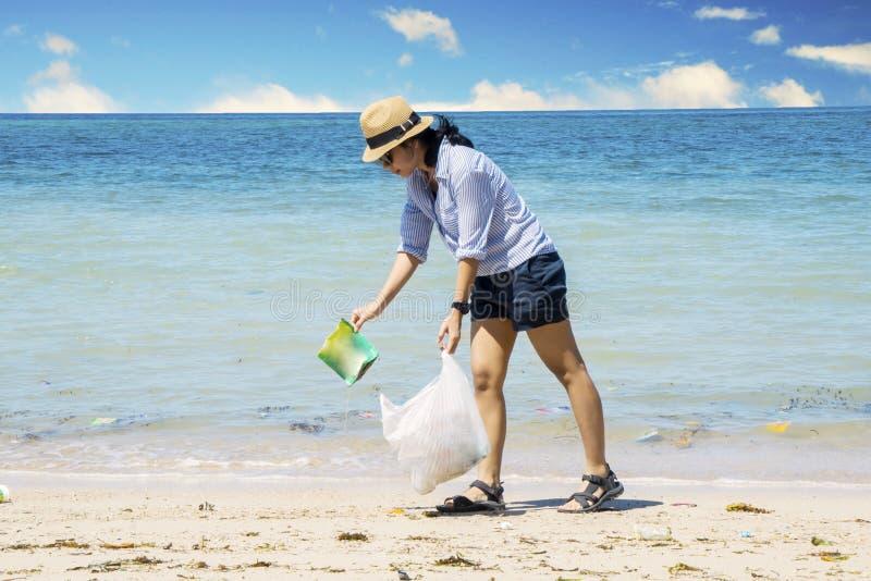 采摘在海滩的年轻女人塑料废物 免版税库存照片