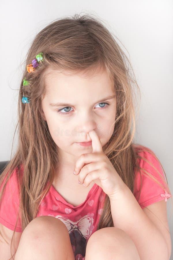 采摘她的鼻子的一个小女孩的画象 库存照片