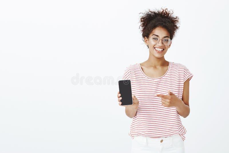 采摘这个电话模型 满意的愉快的非裔美国人的妇女画象玻璃和镶边T恤杉的,显示 免版税库存照片