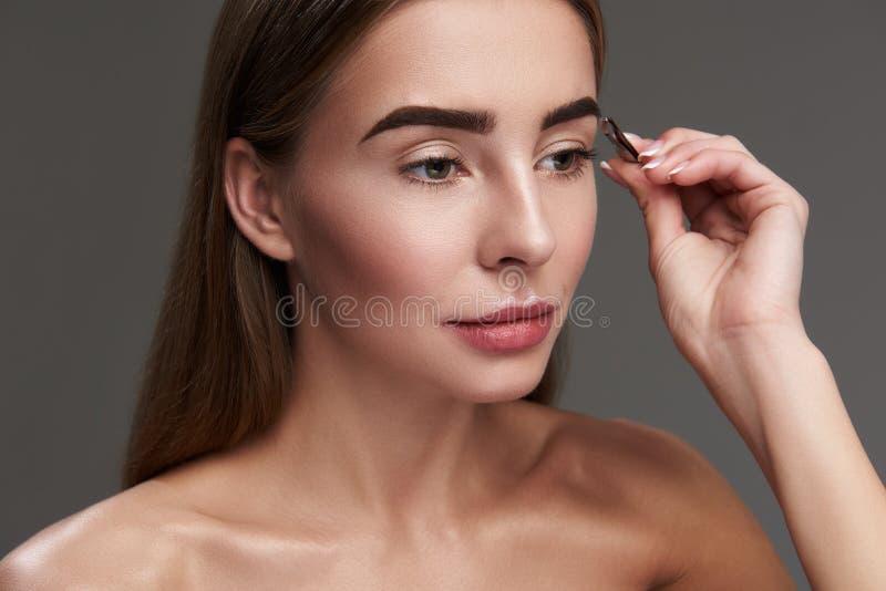 采有镊子的美丽的少女眼眉 库存图片