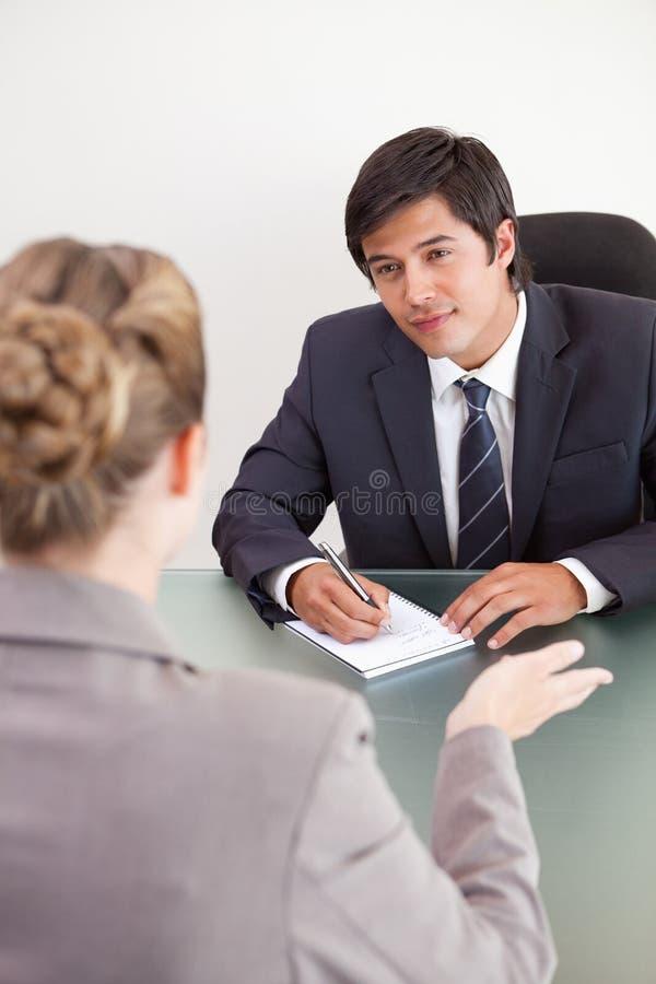 采访一个微笑的经理的纵向一个女性申请人 免版税库存照片