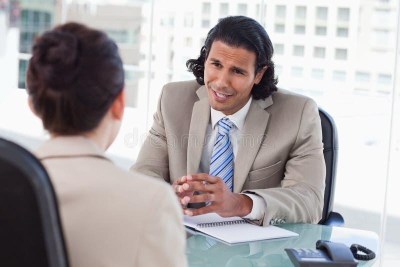 采访微笑的经理一个女性申请人 免版税图库摄影