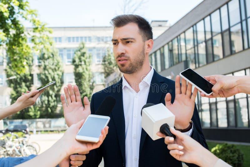 采访的新闻工作者与话筒的严肃的商人 免版税库存照片