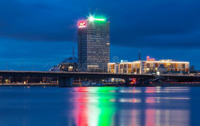 里加现代大厦夜视图与风景水反射的在道加瓦河河水,拉脱维亚 免版税库存照片