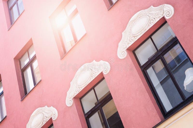 里加老城区一栋红色历史建筑的正面有部分灯光,反射出窗玻璃 系列 — 旧里加T 免版税库存图片