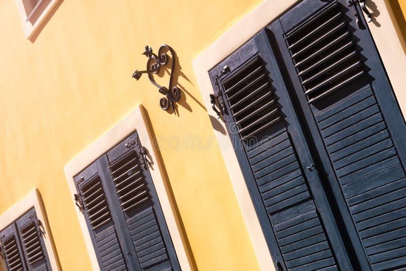 里加老城区一栋红色历史建筑的正面有部分灯光,反射出窗玻璃 系列 — 旧里加T 库存照片