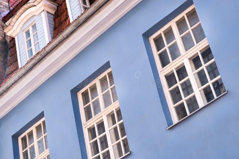 里加老城区一栋红色历史建筑的正面有部分灯光,反射出窗玻璃 系列 — 旧里加T 图库摄影
