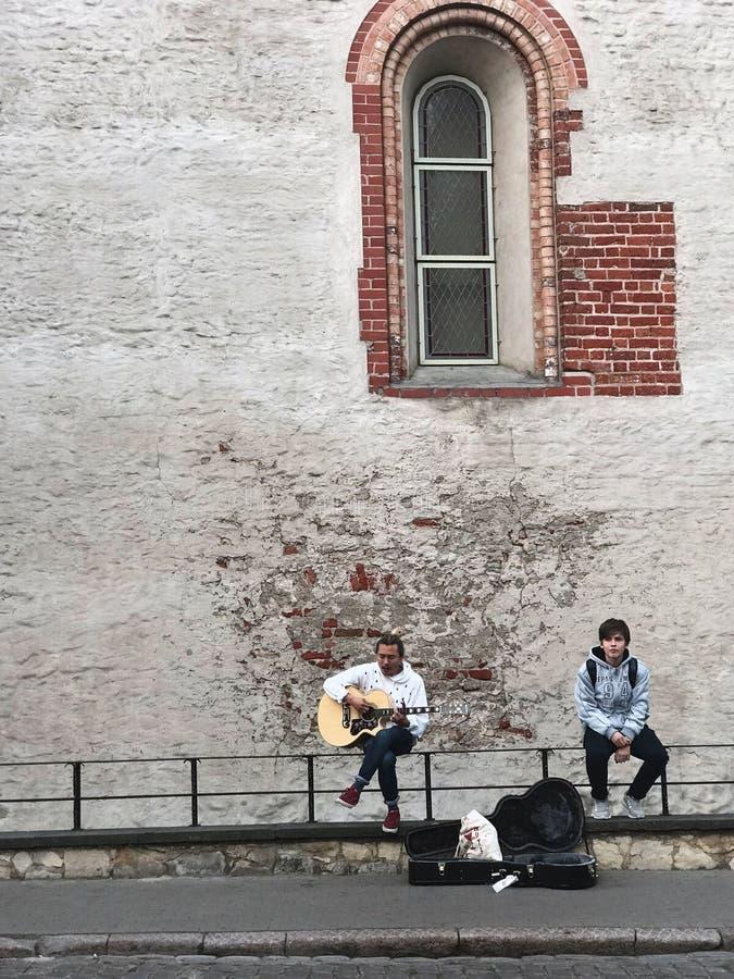 里加,拉脱维亚,2018年9月18日 一个人弹吉他并且唱一首浪漫歌曲,第二个听 在案件附近从 免版税库存照片