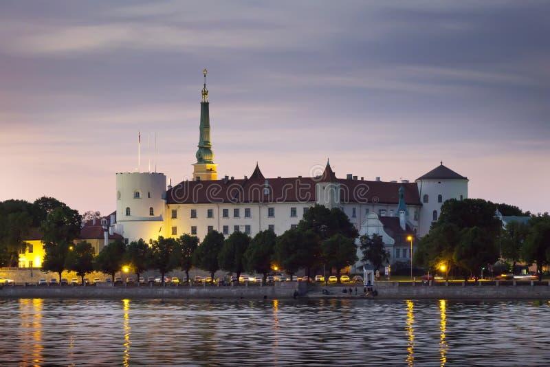里加,拉脱维亚 在道加瓦河上望着城堡的夜景 免版税库存图片