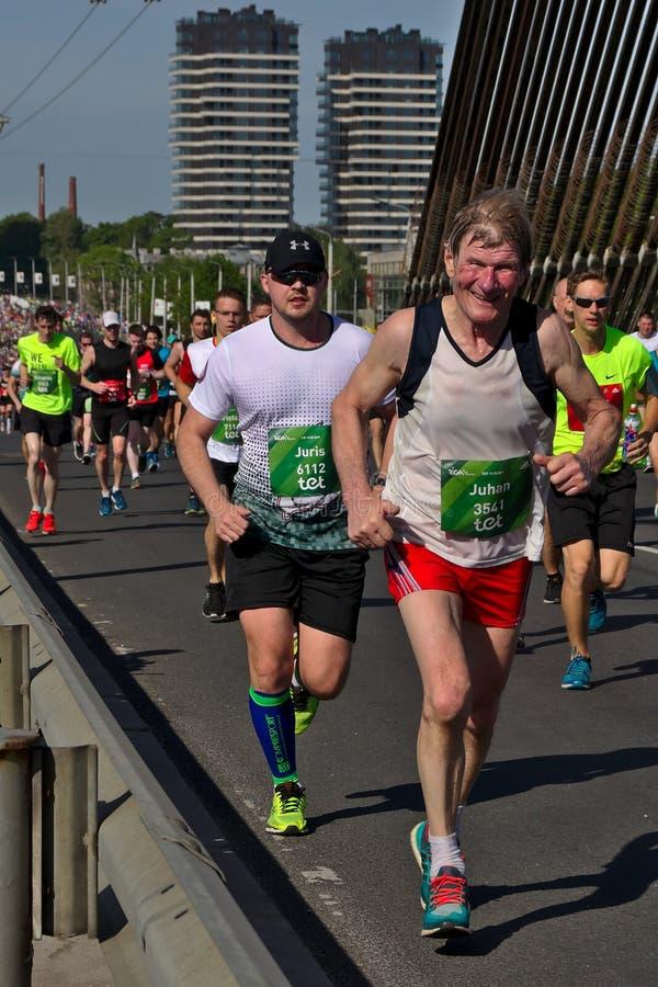 里加,拉脱维亚- 2019年5月19日:勇敢地过桥梁的年长马拉松运动员 免版税库存照片