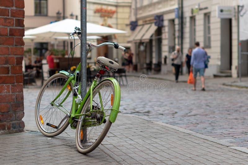 里加,拉脱维亚- 2018年7月26日:在老镇,一辆绿色自行车被锁对铁杆 库存照片