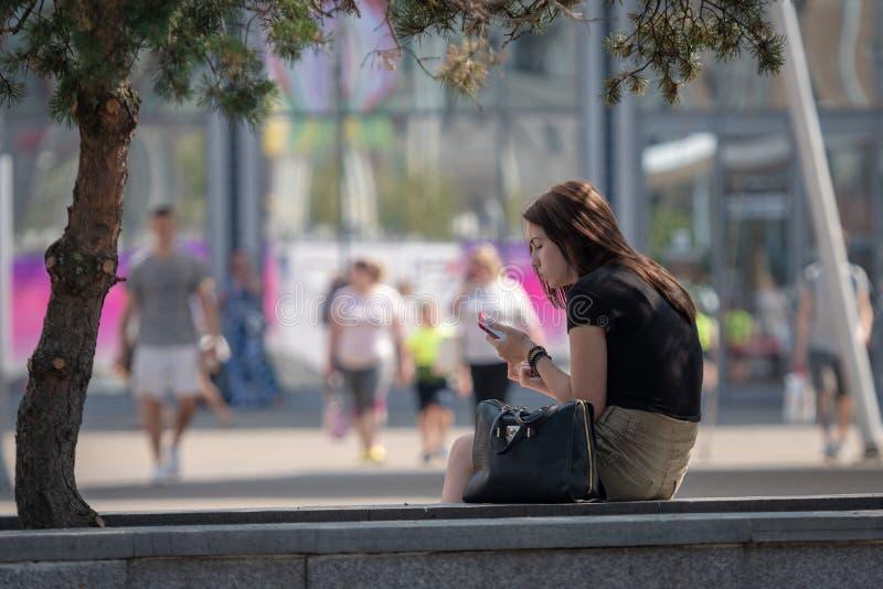 里加,拉脱维亚- 2018年7月18日:年轻女人坐长凳在街道的边缘和神色在电话 免版税库存照片
