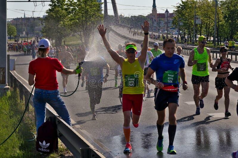 里加,拉脱维亚- 2019年5月19日:愉快马拉松的男性的参加者虽则跑喷水 库存图片
