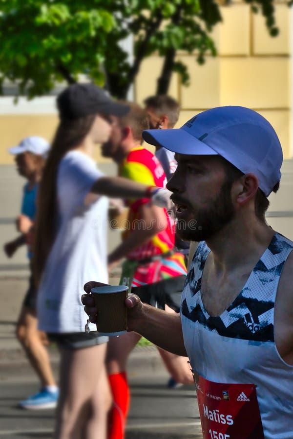 里加,拉脱维亚- 2019年5月19日:跑与杯子的有胡子的人在他的手上 库存照片
