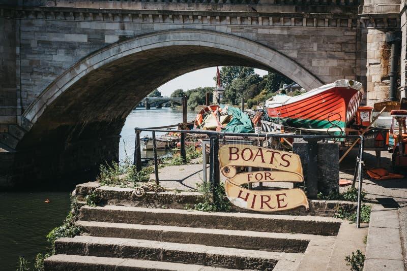 里士满桥梁小船在泰晤士河河沿的聘用标志  库存图片