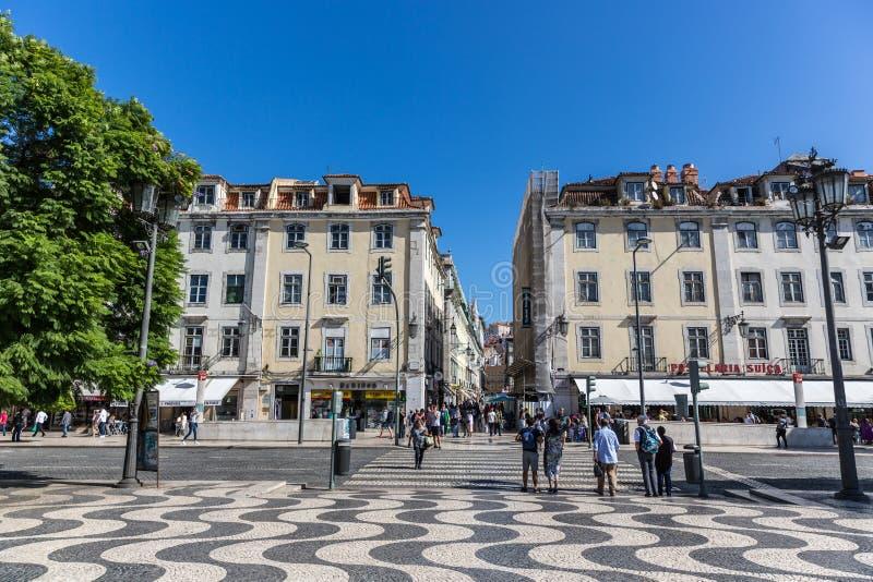 里斯本、葡萄牙- 2018年5月9日-走在一条传统大道的游人和本机在里斯本街市在一蓝天天, Por 库存图片