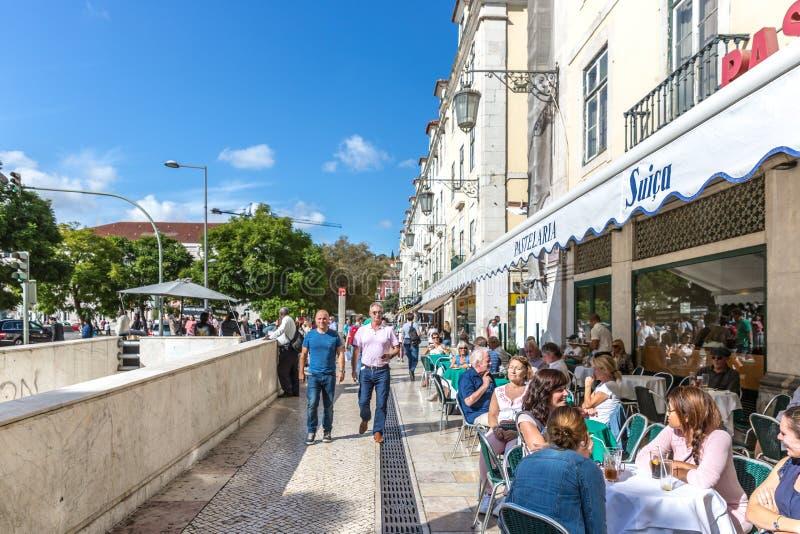 里斯本、葡萄牙- 2018年5月9日-走在一条传统路的游人和本机在街市里斯本,餐馆和树我 图库摄影