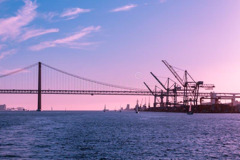 里斯本湾的粉红色紫天,港口和桥梁,海洋工业景观 免版税库存照片