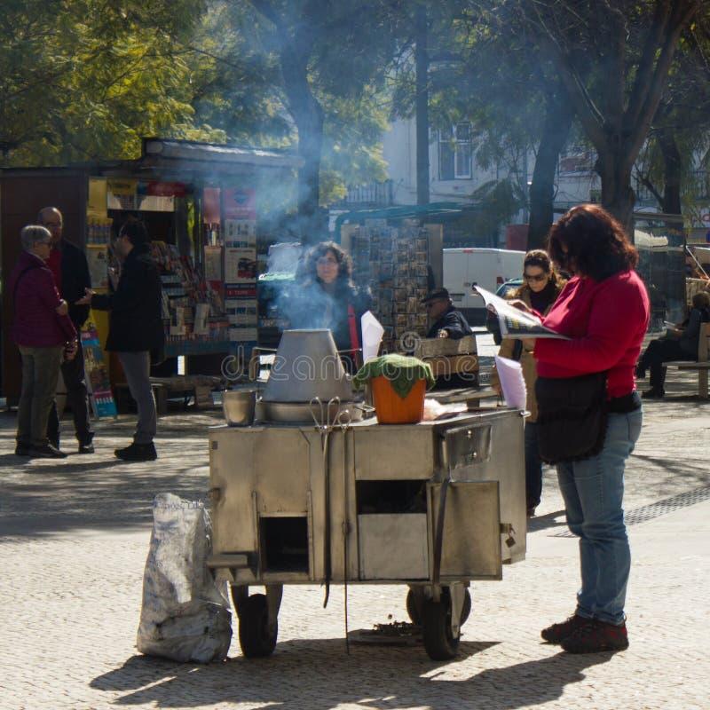 里斯本,葡萄牙:卖烤栗子的叫卖小贩妇女在Rossio 免版税库存图片