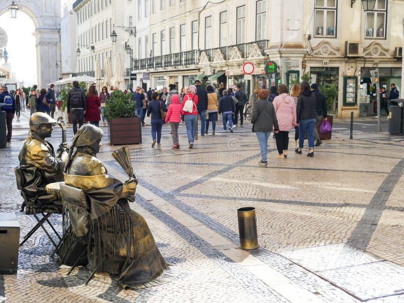 里斯本,葡萄牙:在大街上的居住的雕塑在游人中 图库摄影