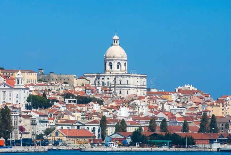 里斯本,葡萄牙- 2010年4月03日:从海的城市视图 教堂和房子晴朗的蓝天的 建筑学和 库存图片