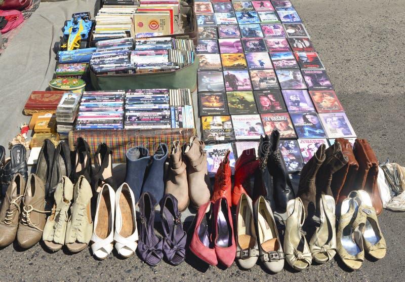 里斯本,葡萄牙- 2017年8月05日:DVD电影妇女老使用的鞋子汇集和堆在跳蚤市场上 图库摄影