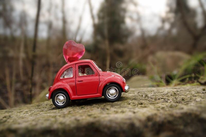 里普斯,德国- 2018年2月1日:有心脏的红色微型汽车在屋顶通过岩石驾驶 免版税库存图片
