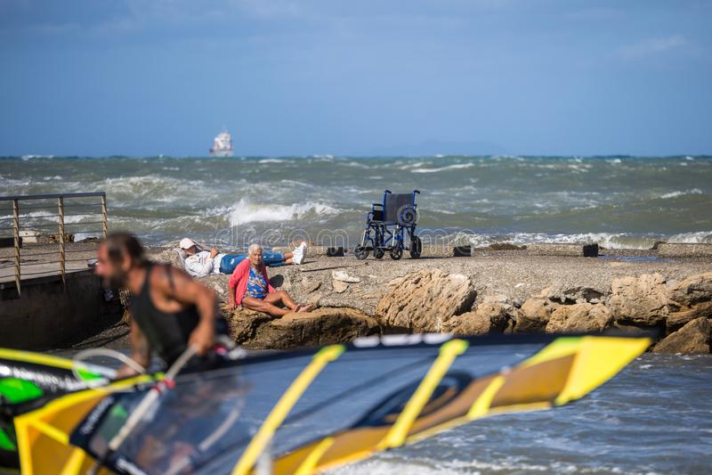 里窝那,意大利- 2017年8月:老妇人坐岩石在海岸线附近看海滩的年轻冲浪者 免版税图库摄影