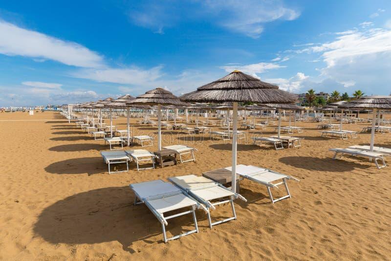 里米尼海滩 阳伞和轻便折叠躺椅在沙子 库存照片
