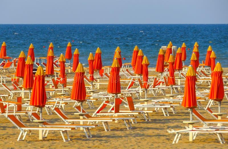 里米尼-橙色伞和sunbeds 库存图片