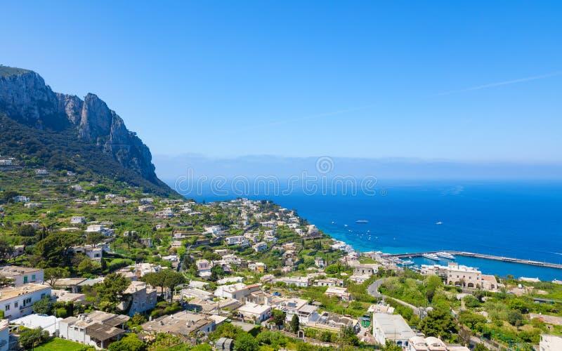 重创的小游艇船坞和岩石卡普里岛海岛,意大利镇住房  免版税库存照片