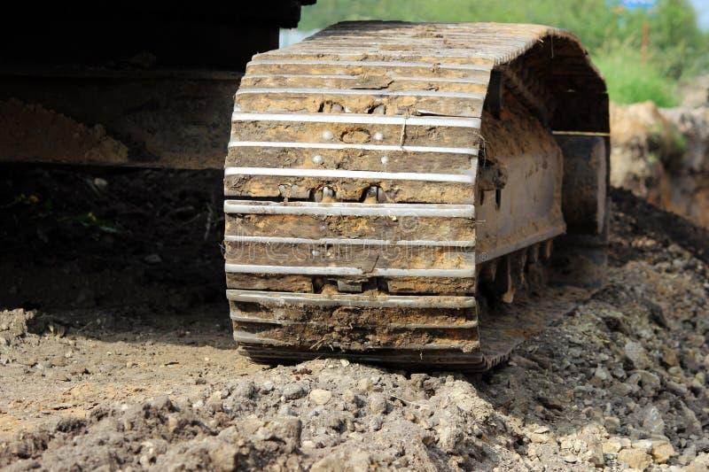 重型建筑设备在站点的履带牵引装置挖掘机毛虫扩展的路 库存照片