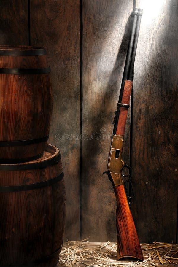 美国西部传奇步枪和威士忌酒桶 库存图片
