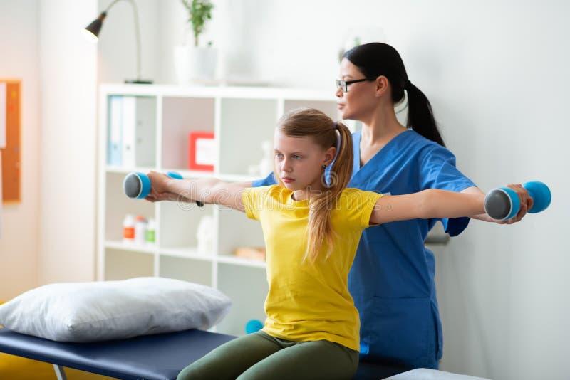 重复活跃护士的姿势黄色T恤杉的努力light-haired女孩 库存照片