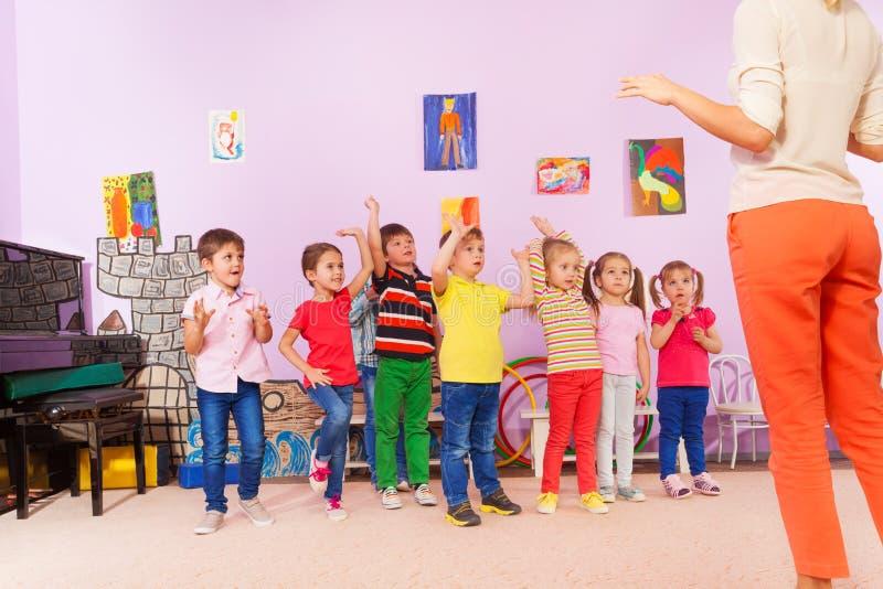 重复锻炼的小组孩子在老师以后 免版税图库摄影