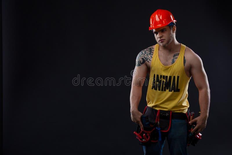 重工业和劳方概念-有确信的面孔表示的人 肌肉性感的专业建造者,安装工 库存照片