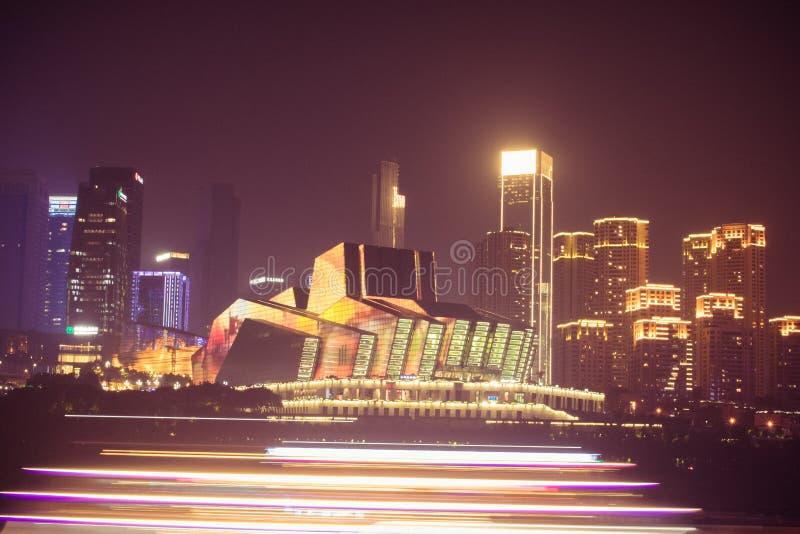 重庆盛大剧院夜景和游轮照明设备在重庆,中国 江北嘴复合体 库存照片