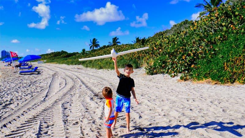 重新开放后,身穿泳衣的快乐男孩在海滩上玩耍和享受 孩子们与飞机一起玩 免版税库存照片